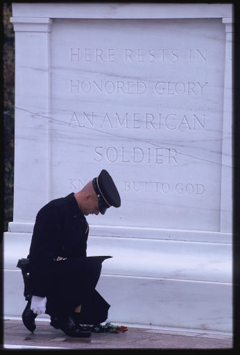 Soldier lays flower at the tomb of the unknown soldier.
