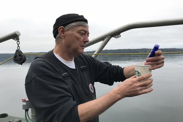 Photo of Doc Thoemke measuring the temperature of the water in the cup,