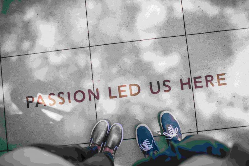 "Looking down at shoes on a sidewalk that says ""Passion Led Us Here"""