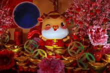 Photo of a cartoon Ox surrounded by Chinese new year decorations.